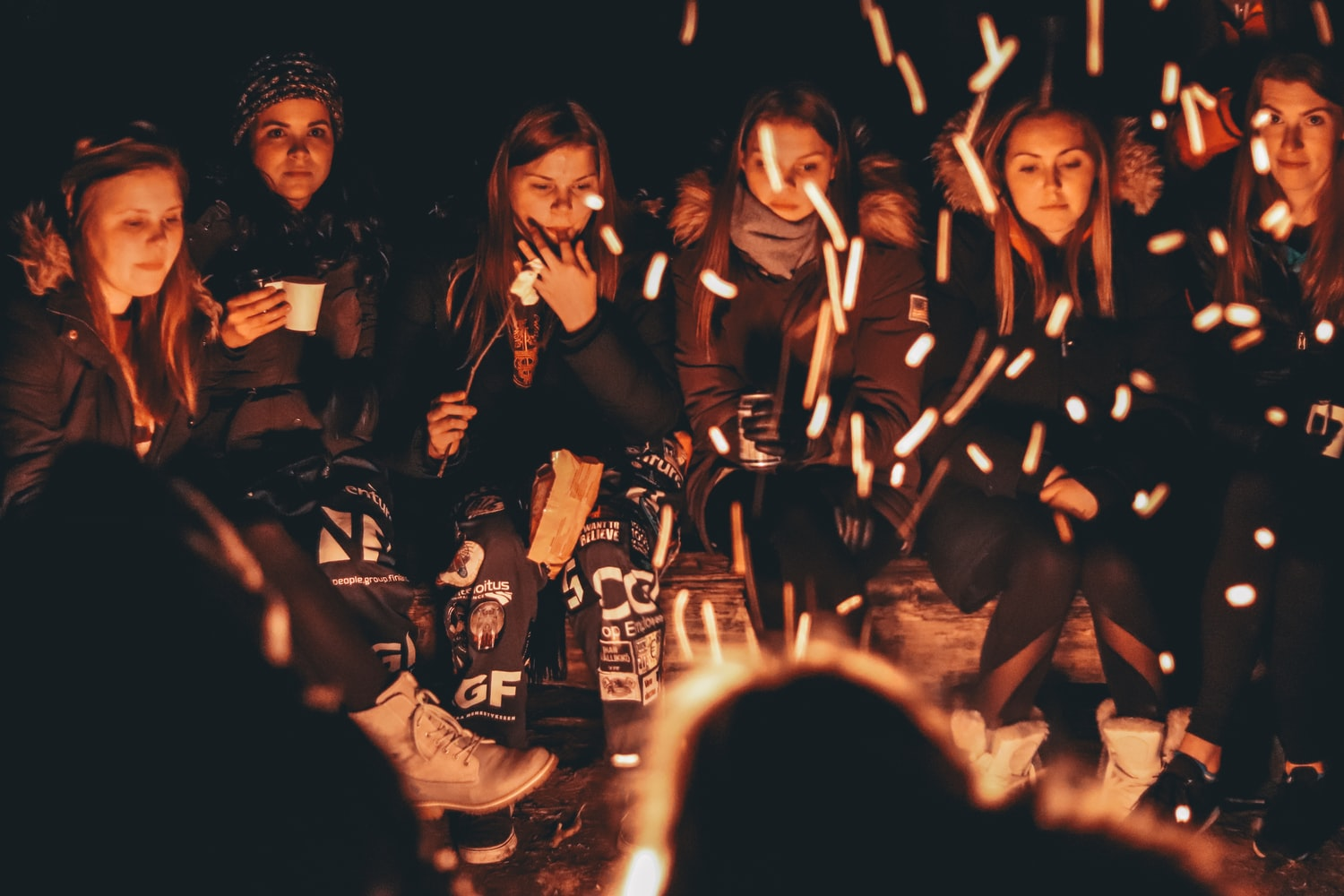 Group of woman wearing a coat and eating some snacks are chatting together with campfire at the center of them