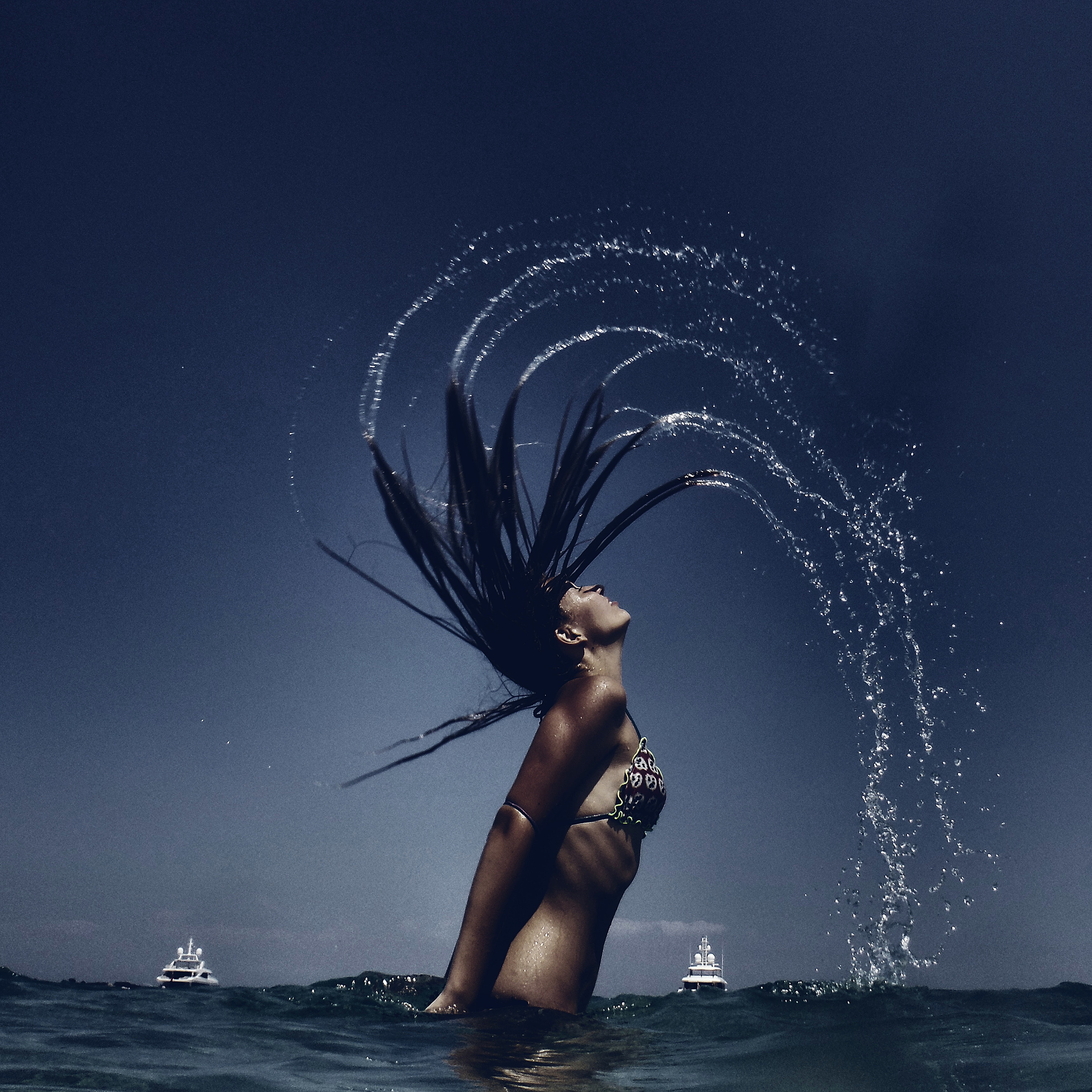 woman flipping hair while soaking in body of water