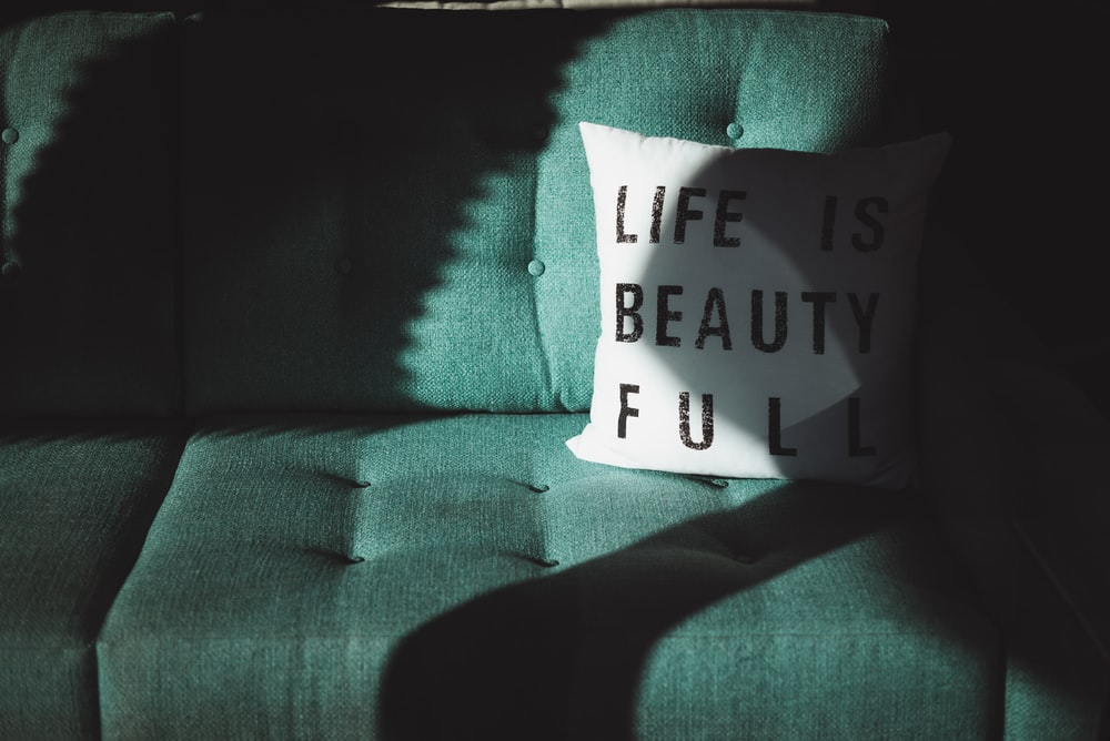 white and black Life is beautifull throw pillow on top of sofa