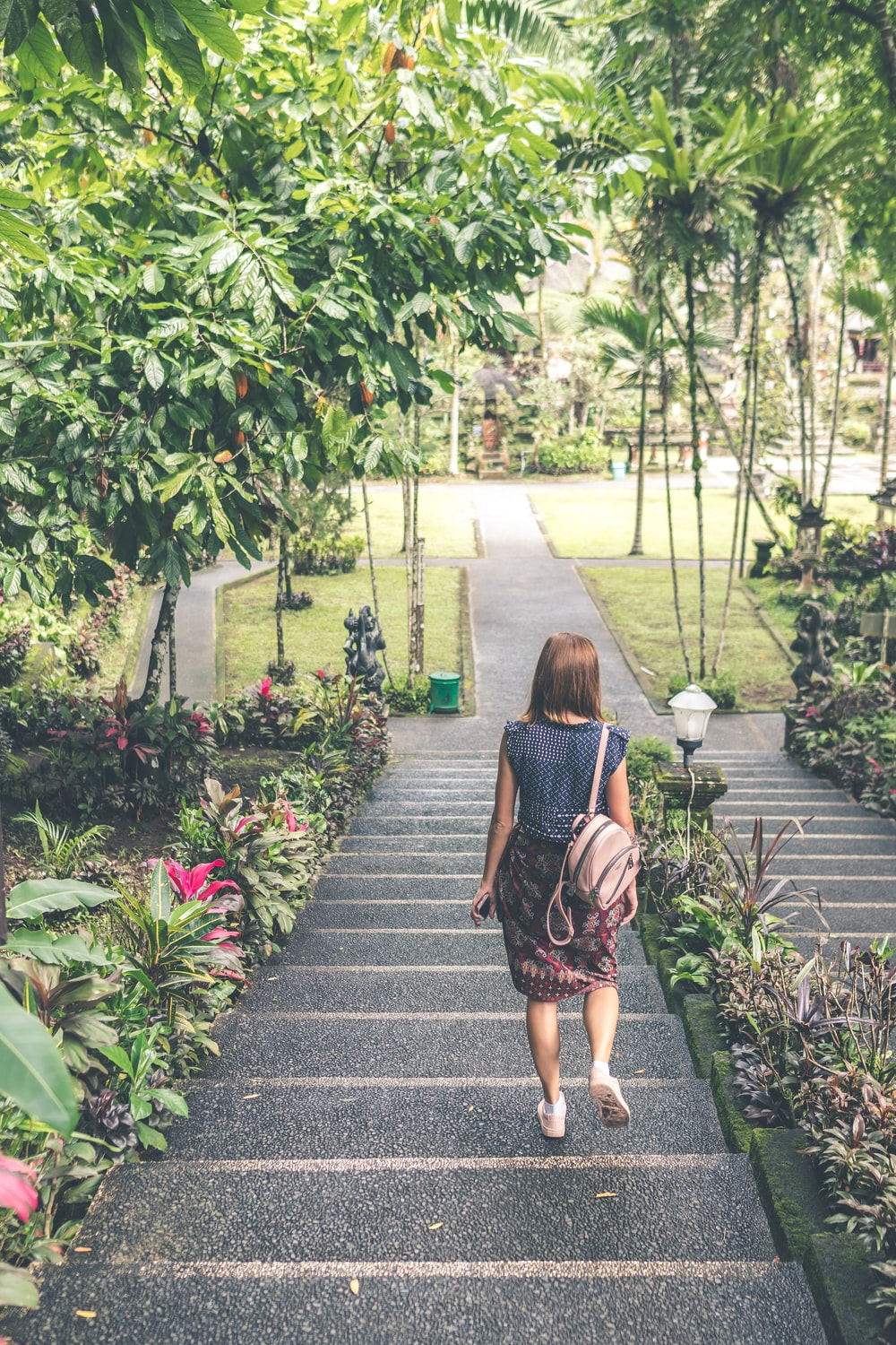 woman walking down on concrete stairs near garden plant during daytime