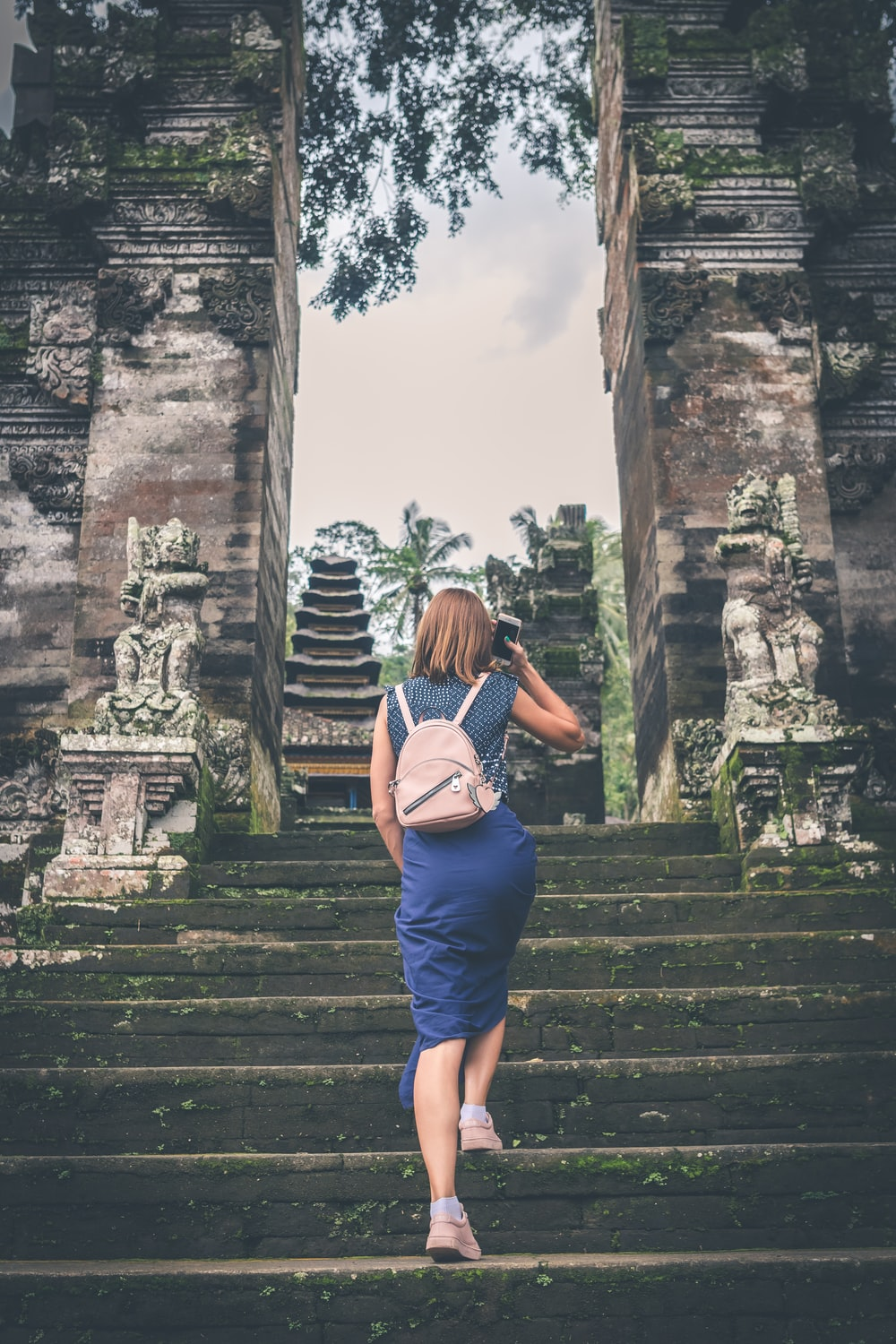 shallow focus photography of woman in blue dress walking towards temple