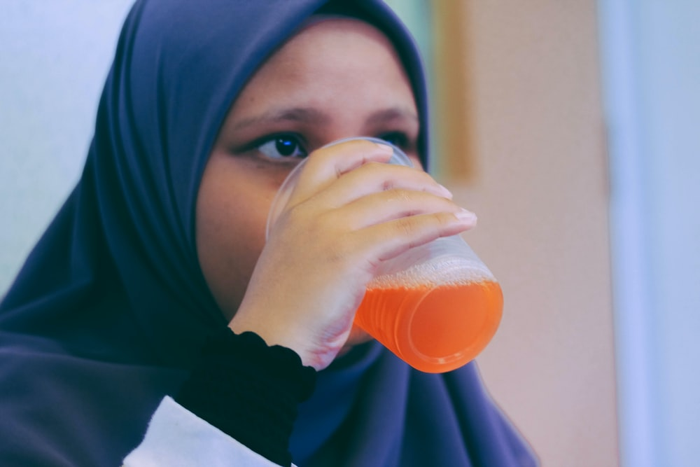 woman in black hijab headdress white drinking