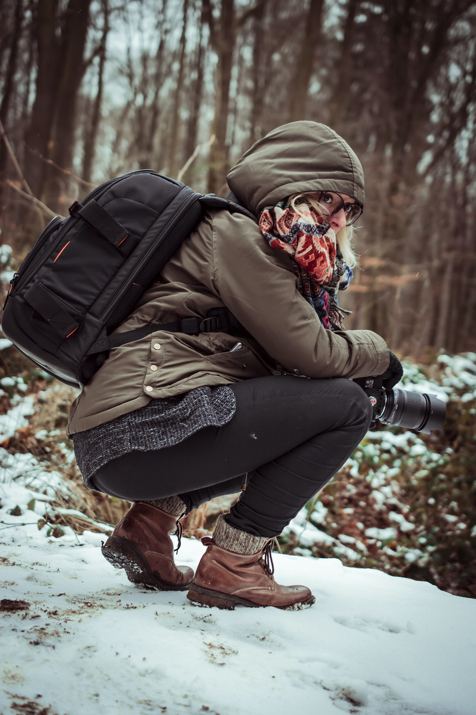 woman in brown hooded jacket holding camera while squatting on snow covered ground during daytime