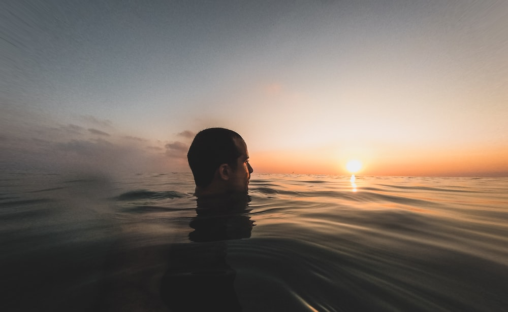 man in water under blue sky during sunset