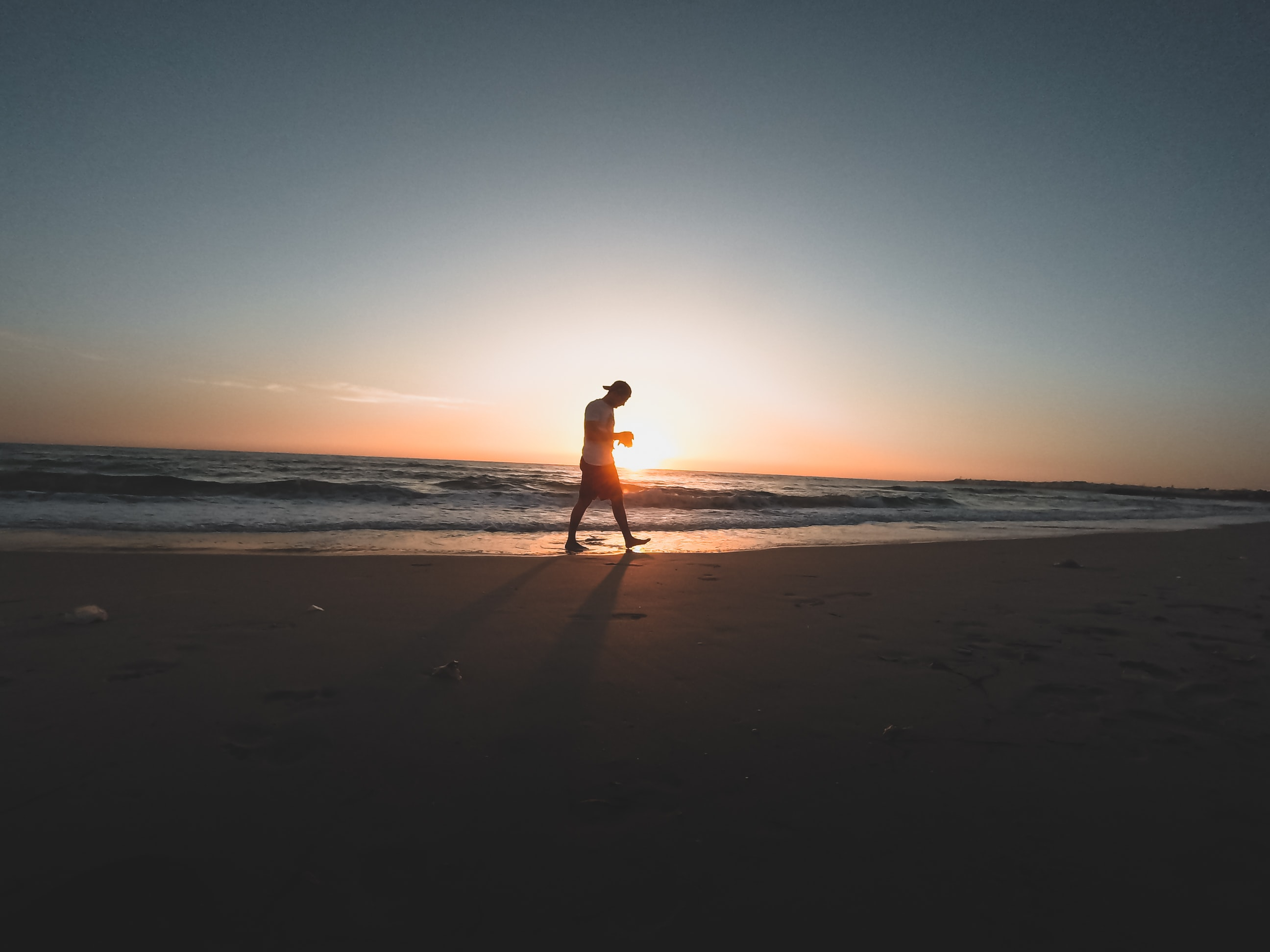 person walking on seashore during daytime