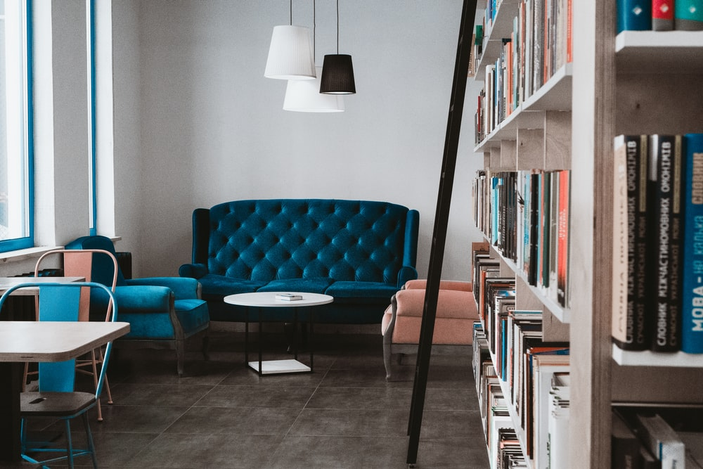 tufted blue 3-seat sofa near white wall and window