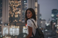 woman in white t-shirt carrying black leather backpack