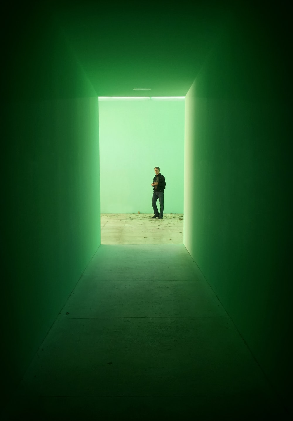 man in black jacket stands near green wall