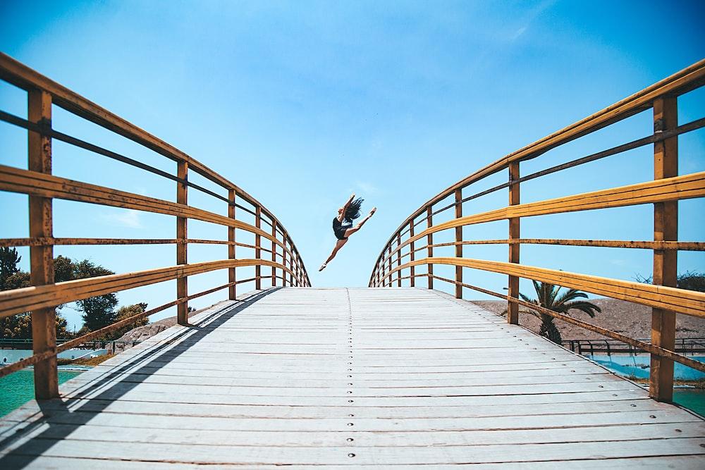 woman jumping near bridge during daytime