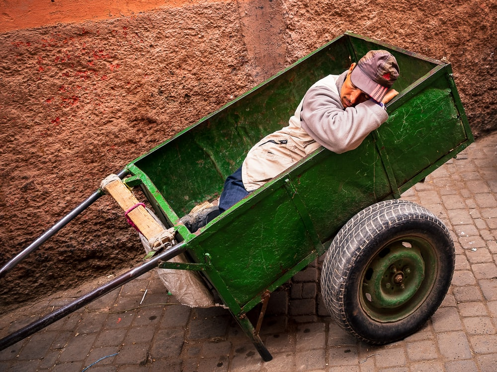 man laying inside green wagon