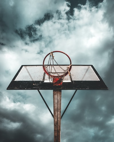low angle photo of white and black metal portable basketball hoop under cloudy sky during daytime