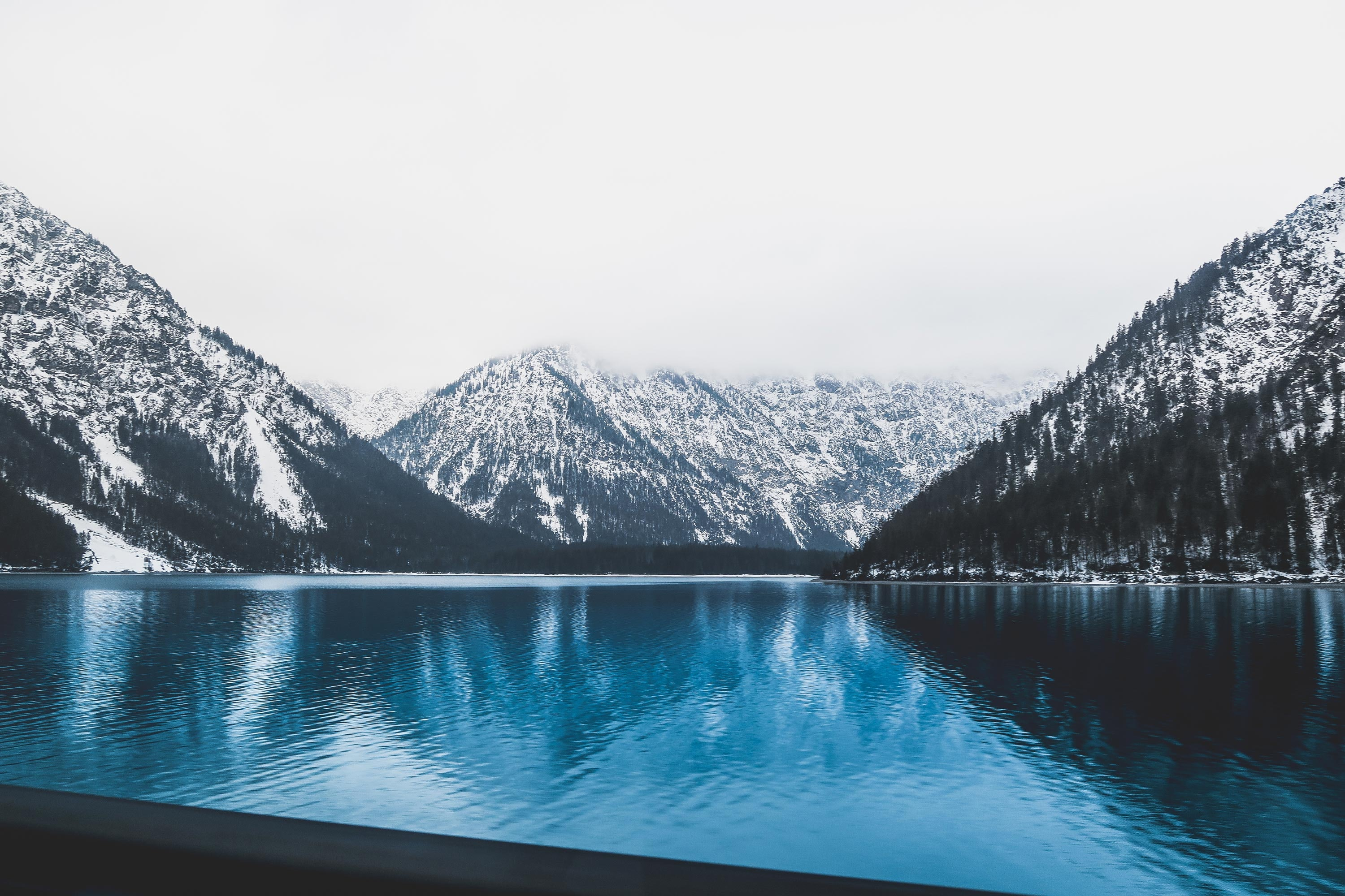 landscape photo of clear blue body of water near mountains covered with snow