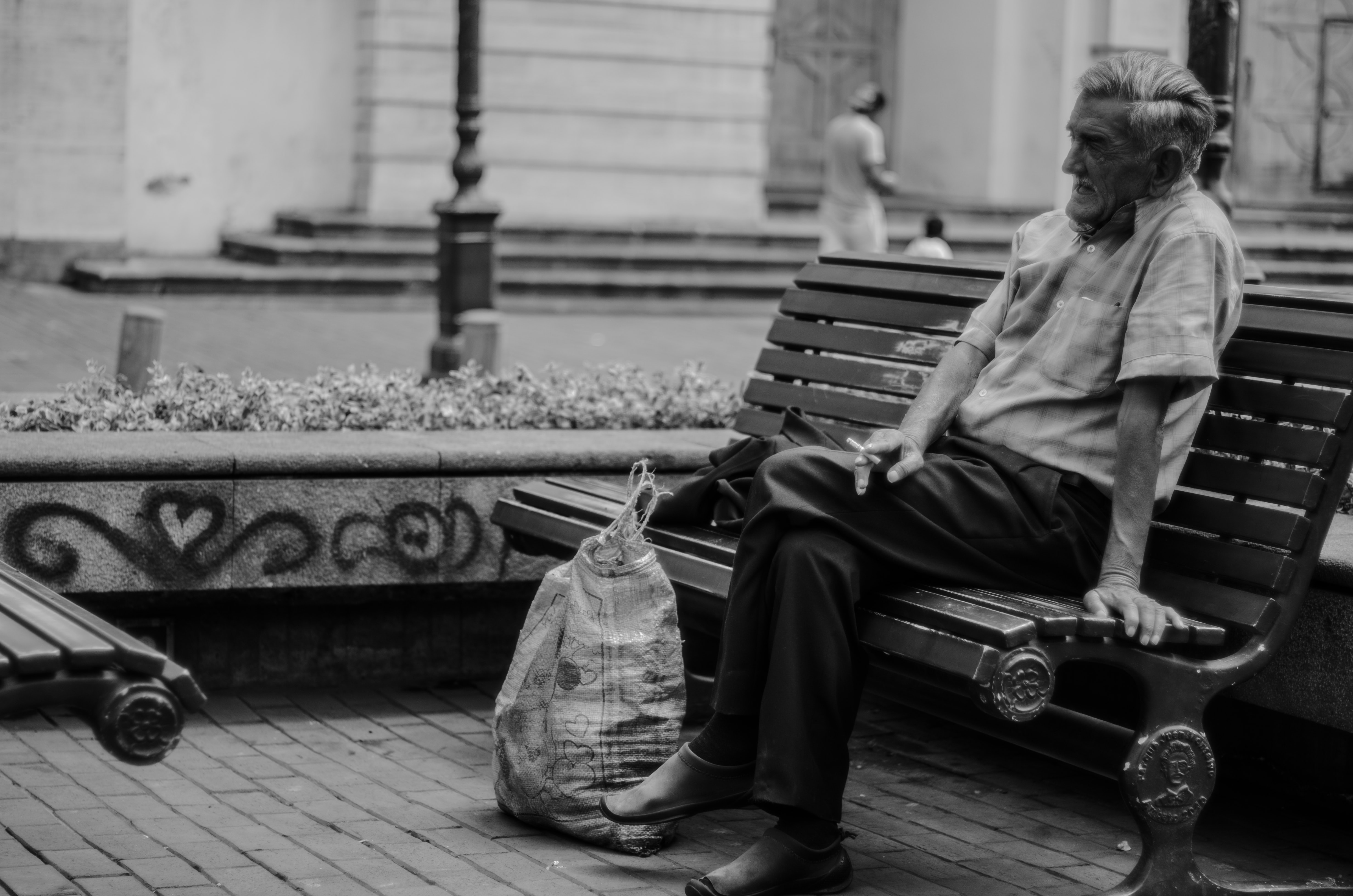 greyscale photography of man sitting on bench