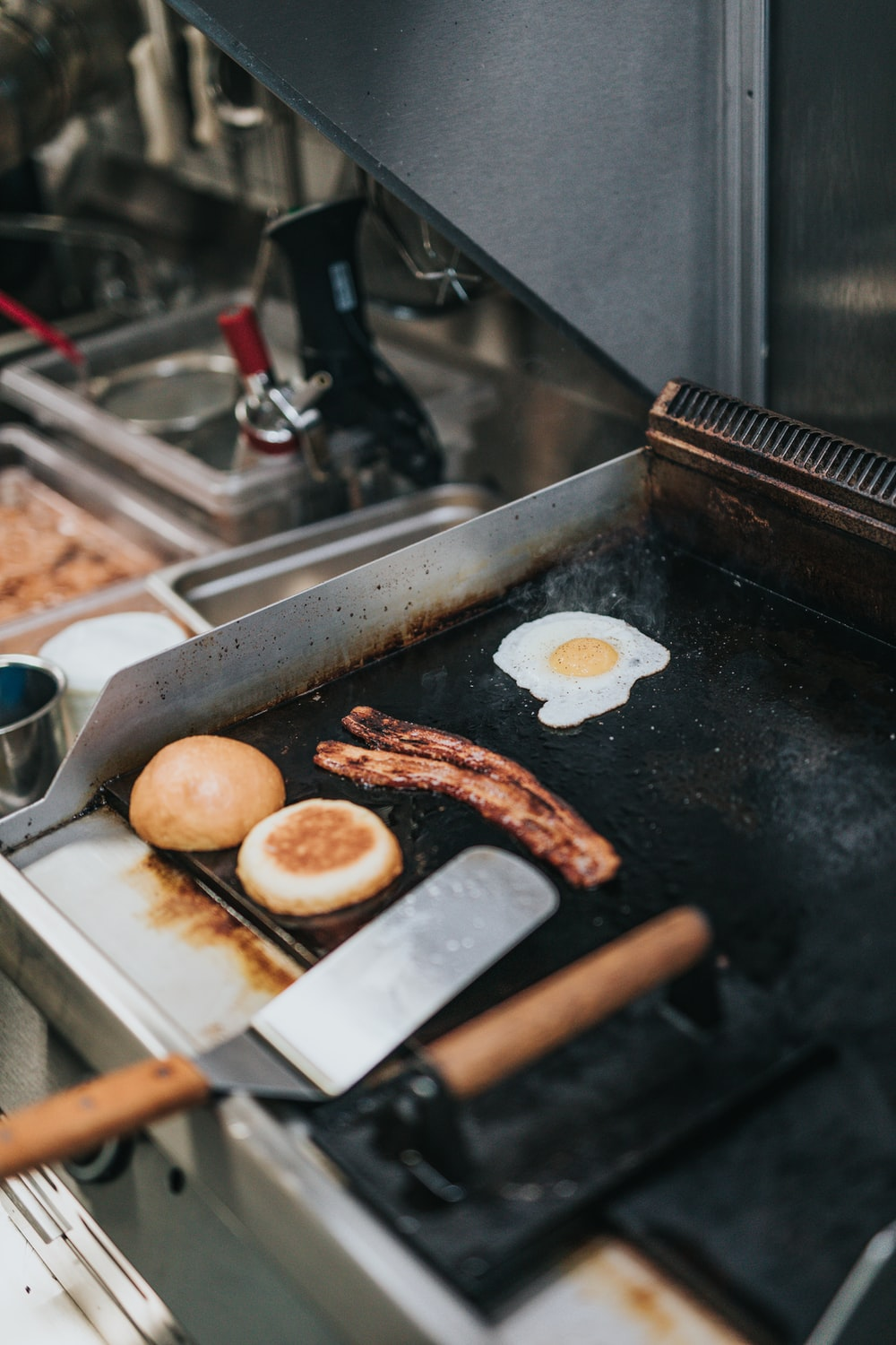 person cooking bacon, egg, and bread
