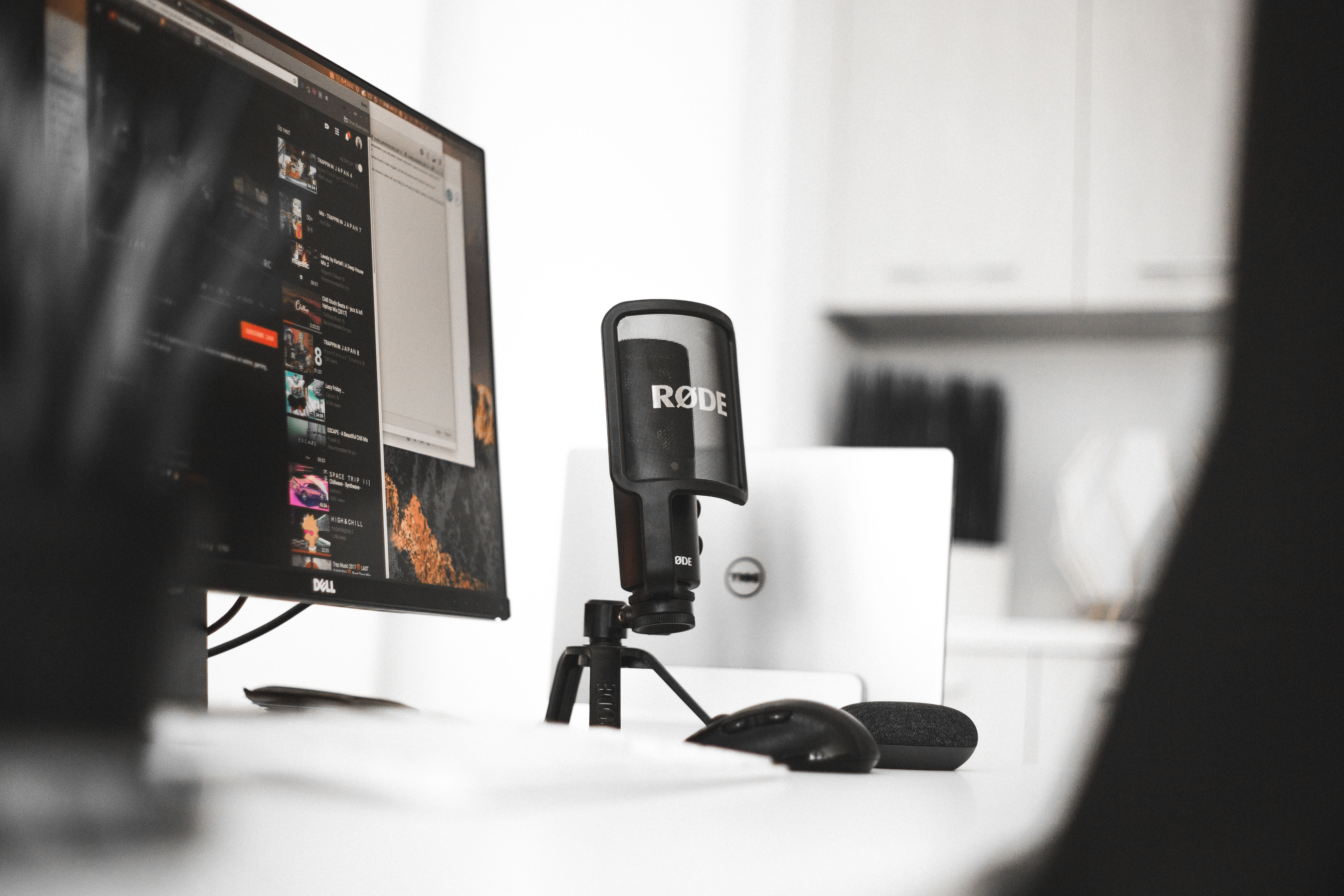 black Rode condenser microphone beside computer monitor