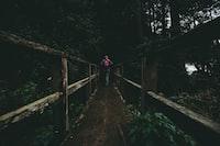 woman walking on wooden bridge