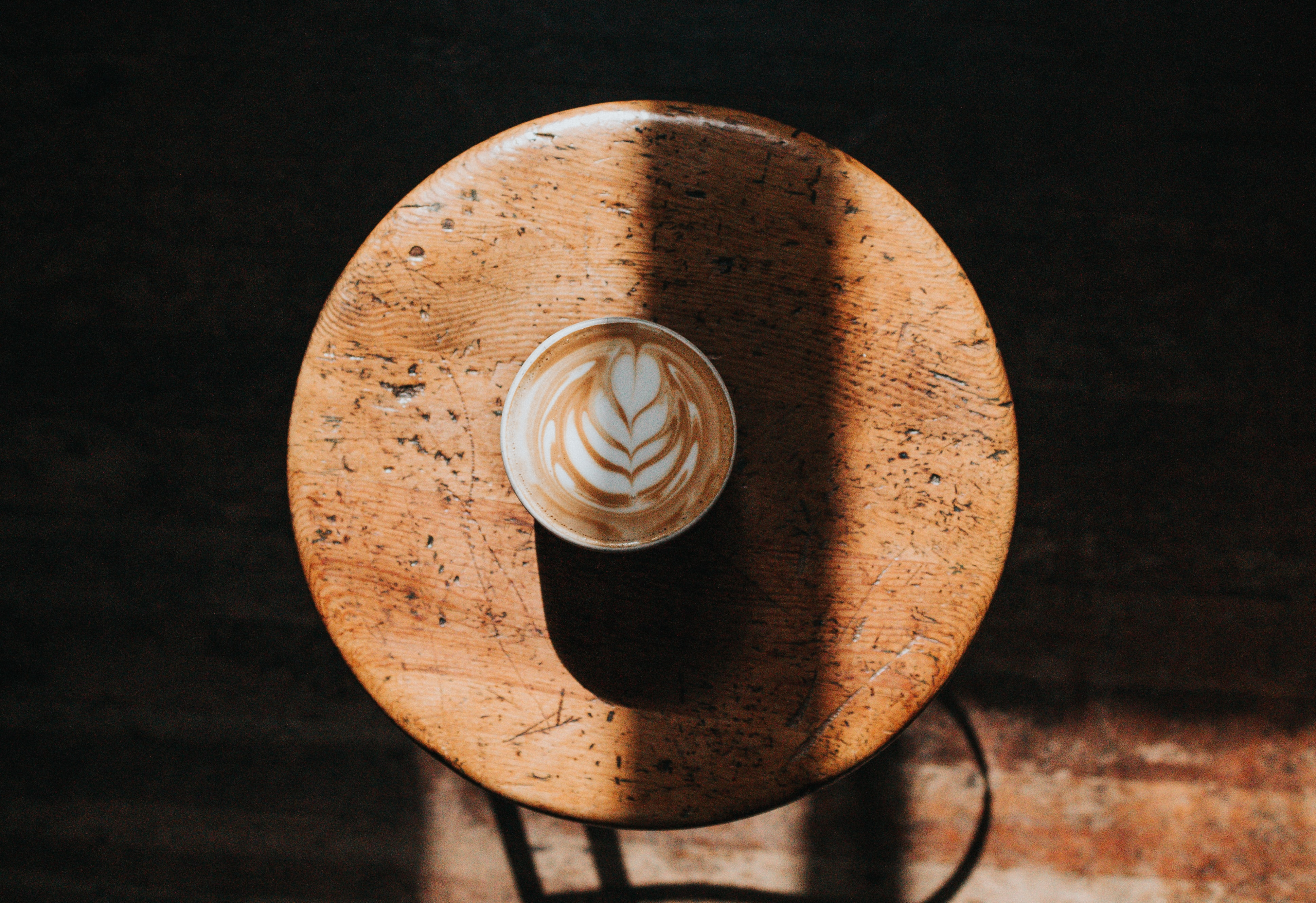 white ceramic cup on brown wooden stool
