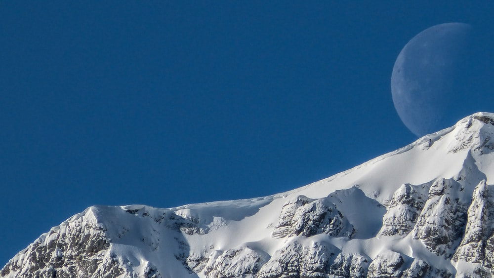 photo of full moon during daytime and ice coated mountain