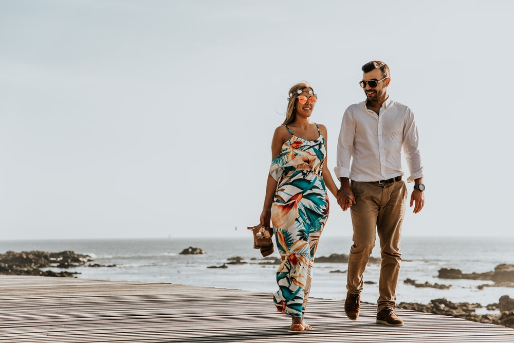 couple walking near sea at daytime