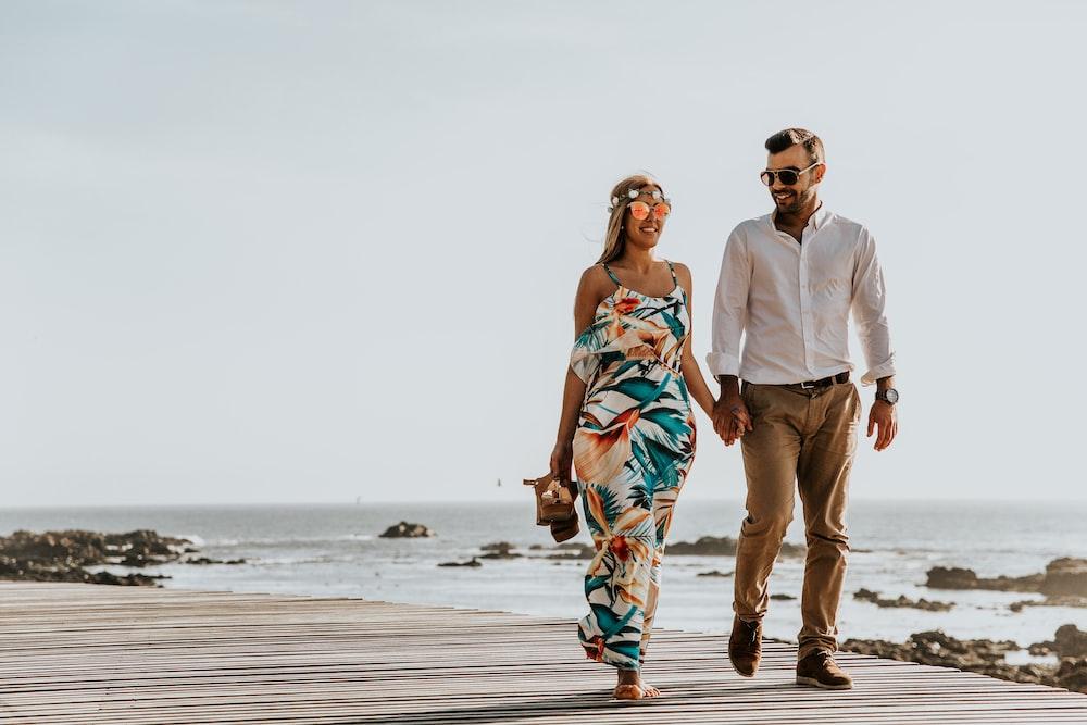 couple walking near sea at daytime