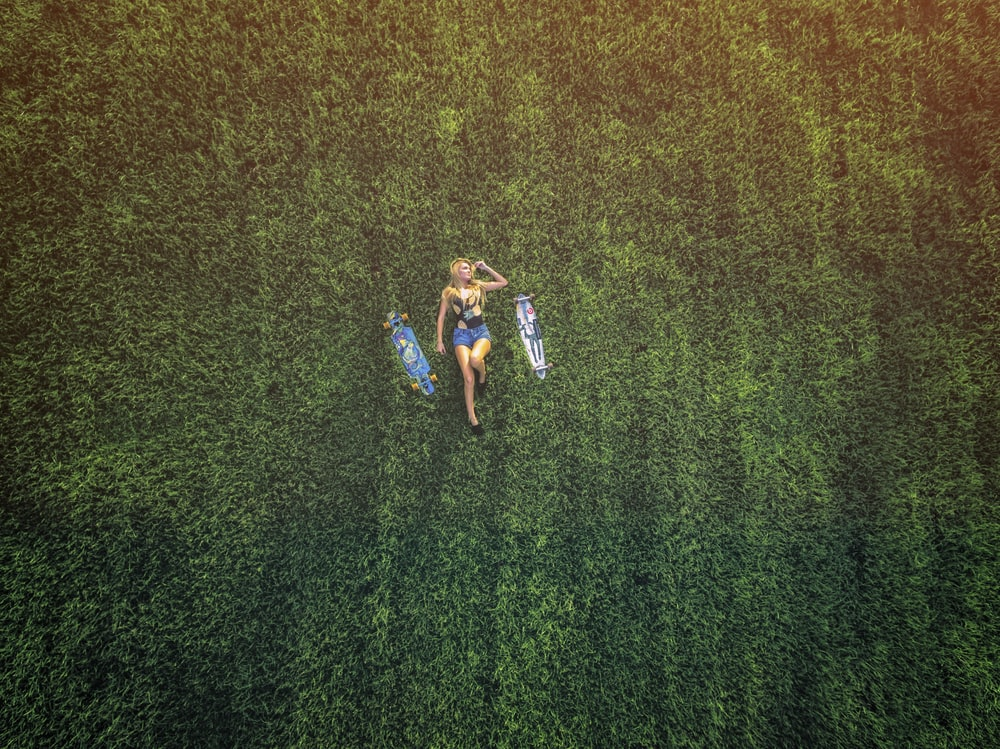 aerial view of woman laying on meadow