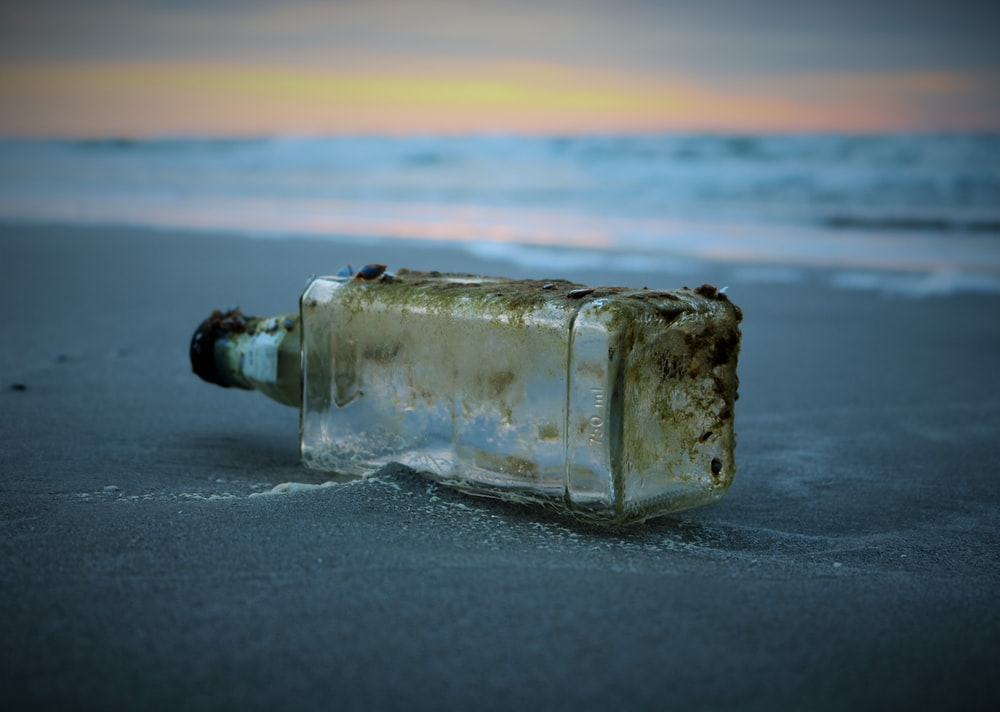 selective focus photography of bottle drifted on shore