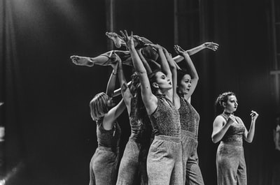 grayscale photo of women dancing performance art teams background
