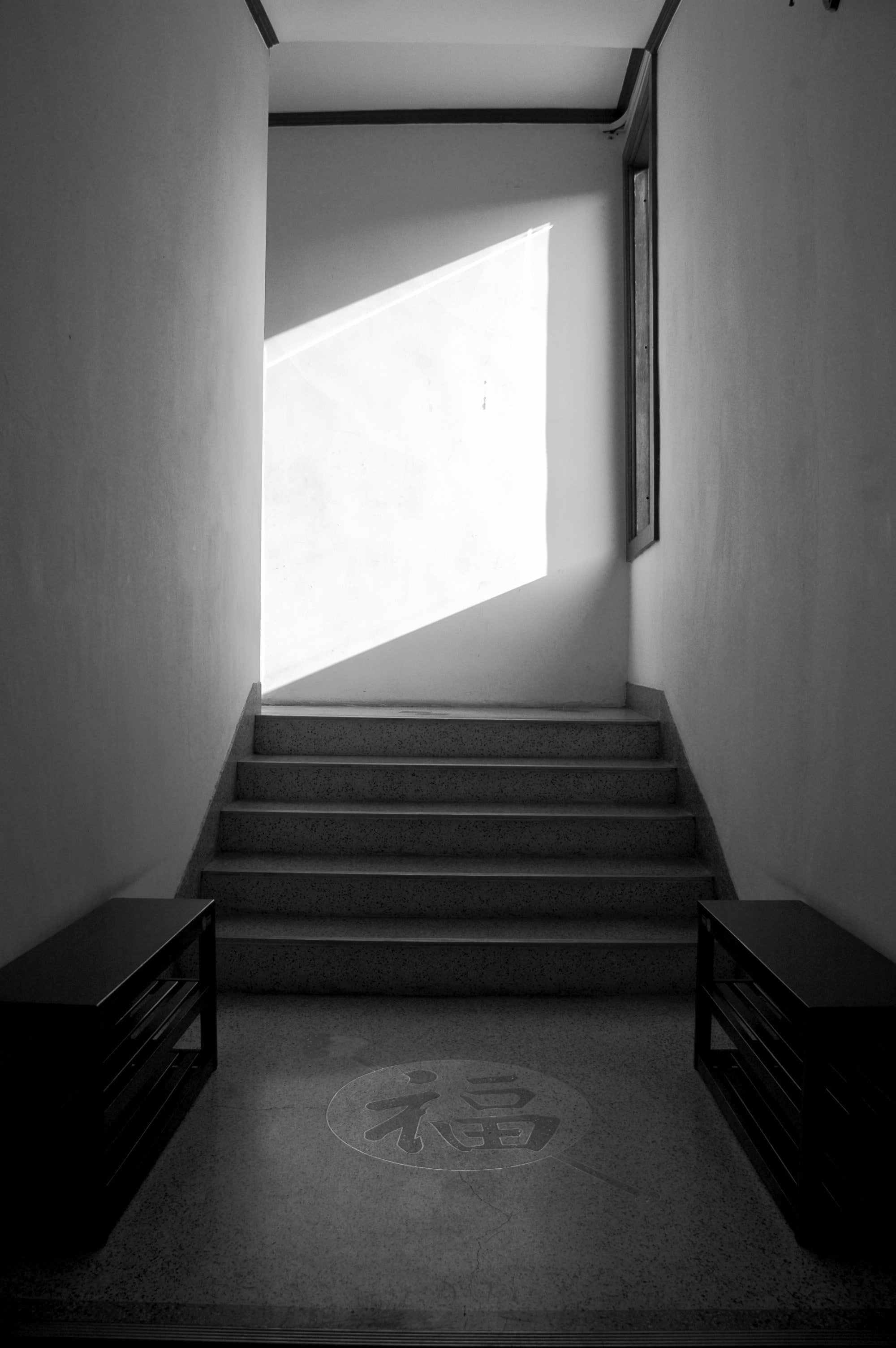 grayscale picture of two bench near kanji on floor and stairs
