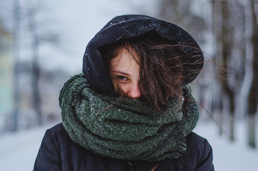woman wearing hoodie under green scarf