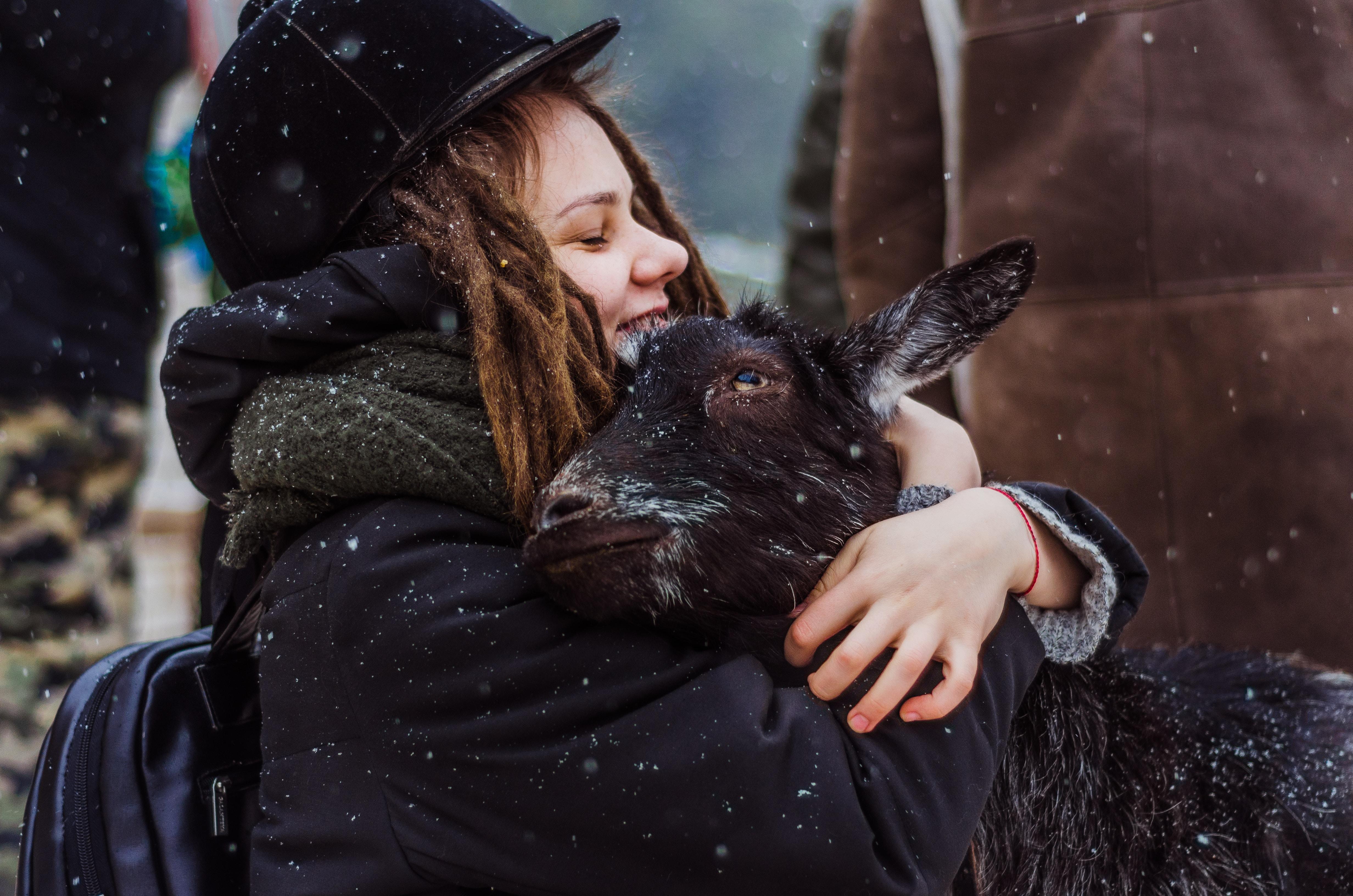 woman cuddling goat