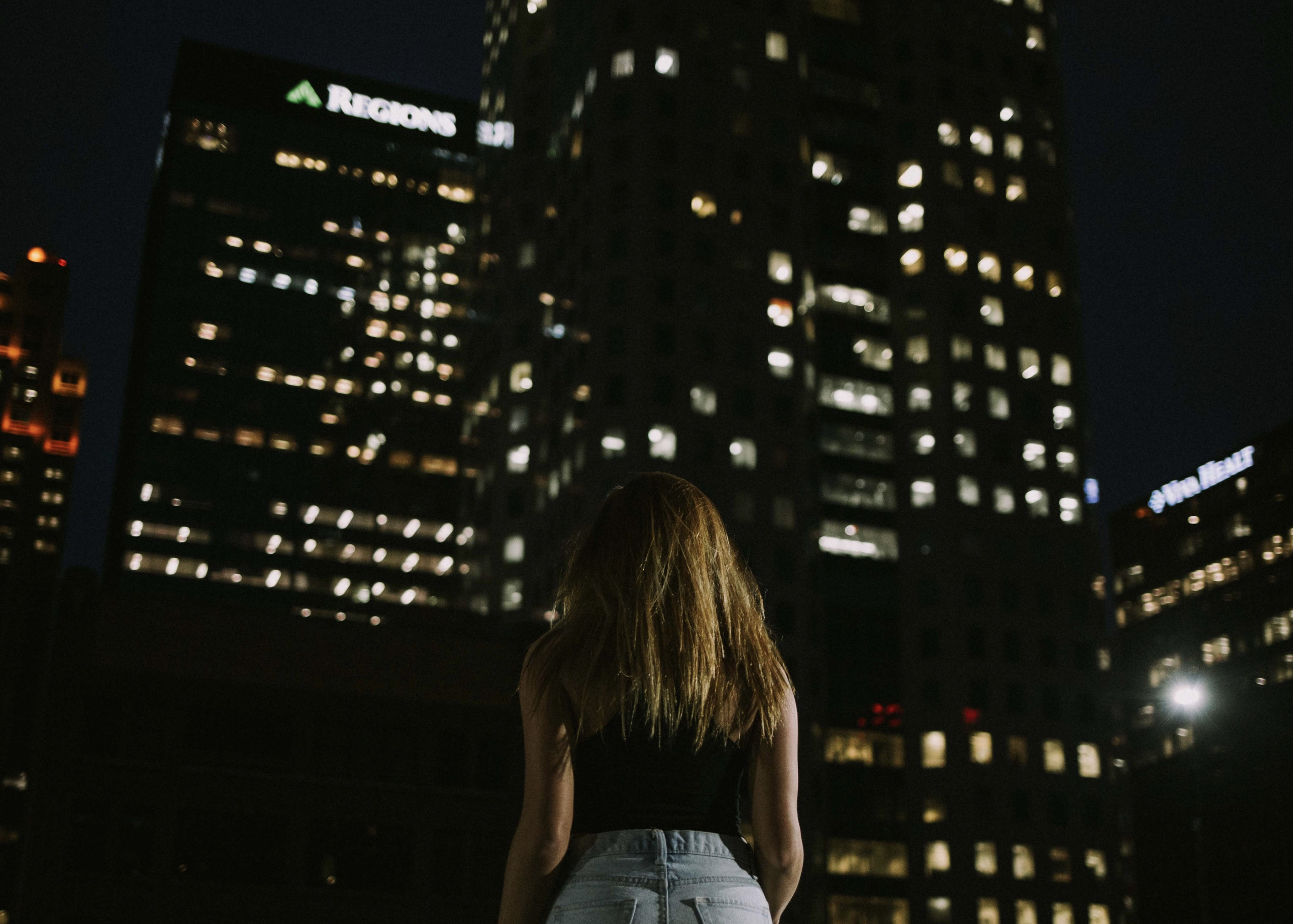 woman stands in front of high-rise buildings