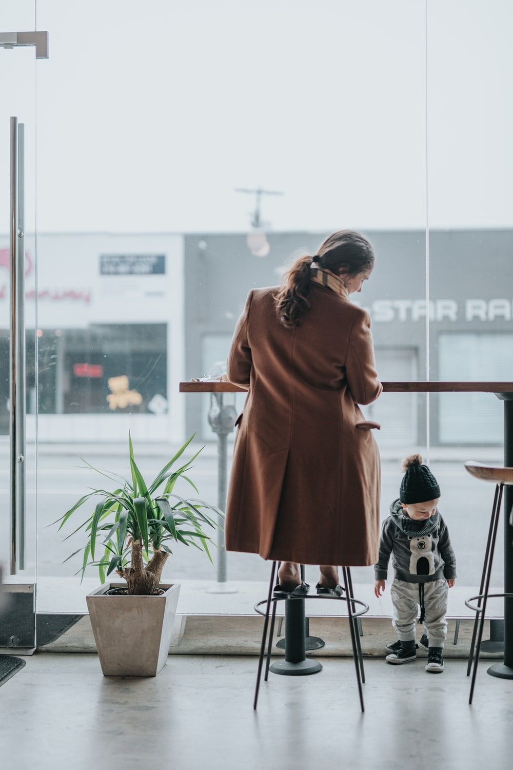 person sitting in stool looking at toddler
