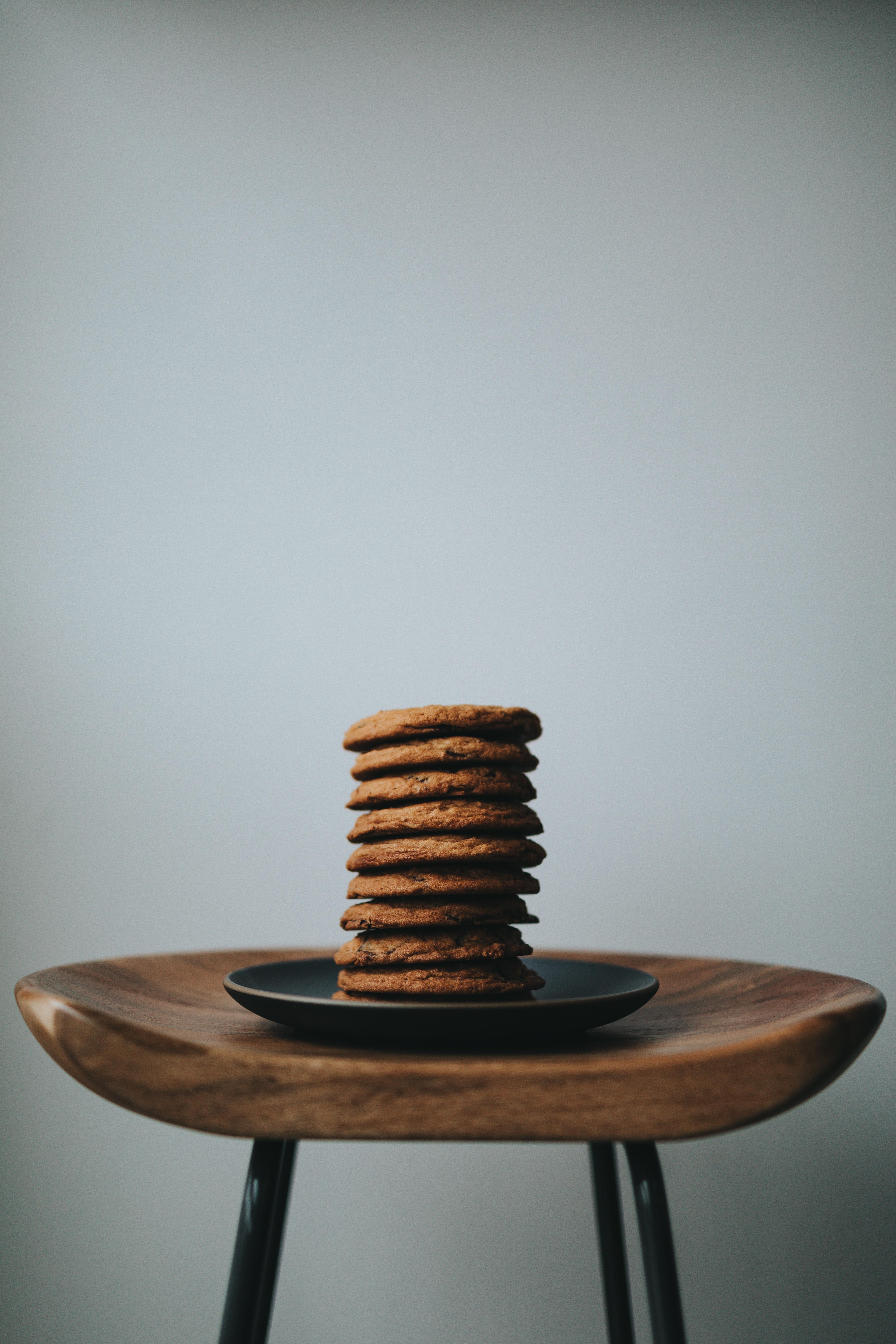 stack of brown cookies on black ceramic plate