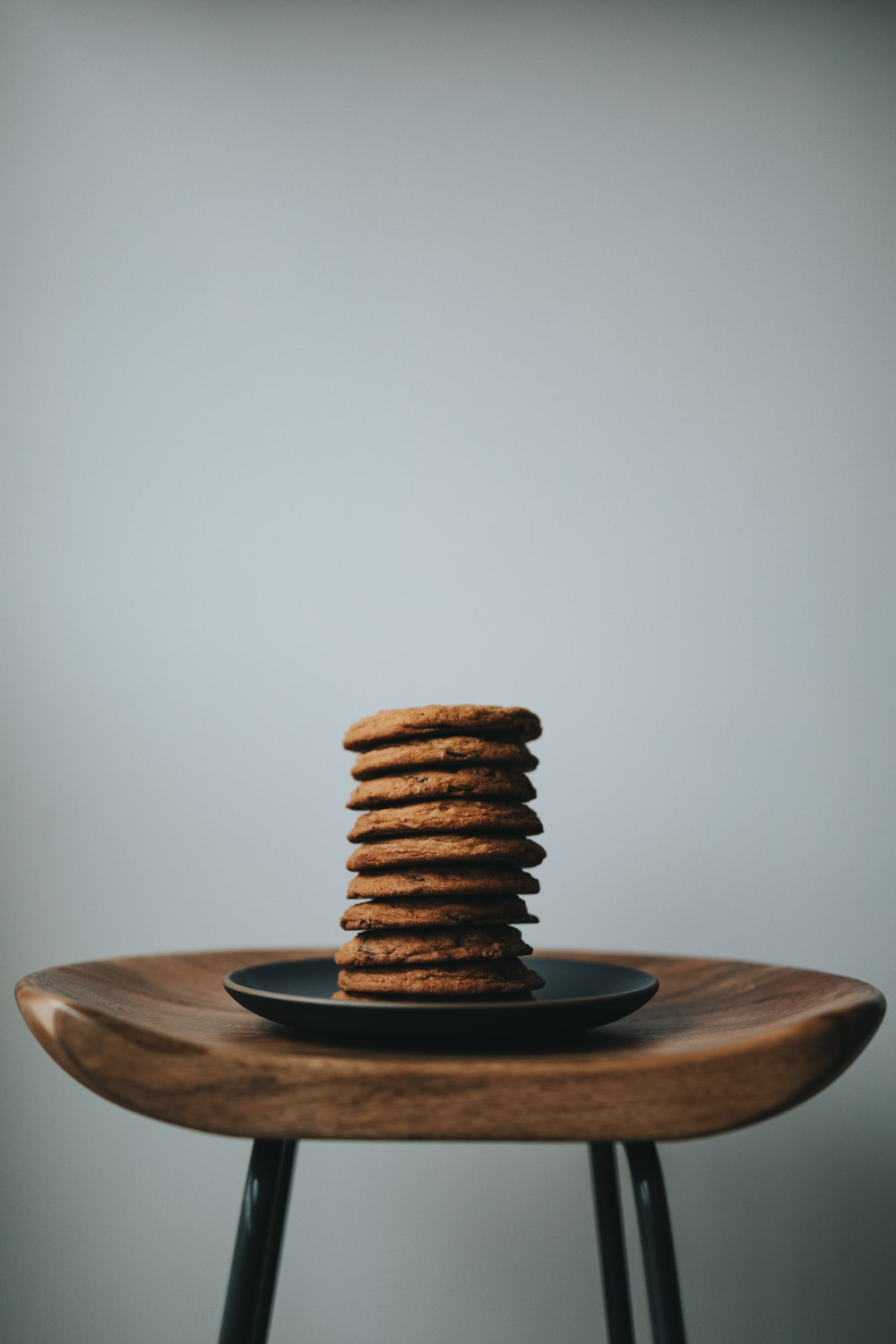 stack of brown cookies on black ceramic plate