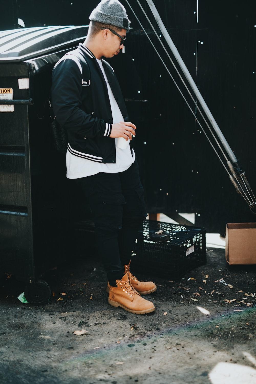 man standing beside black metal dresser