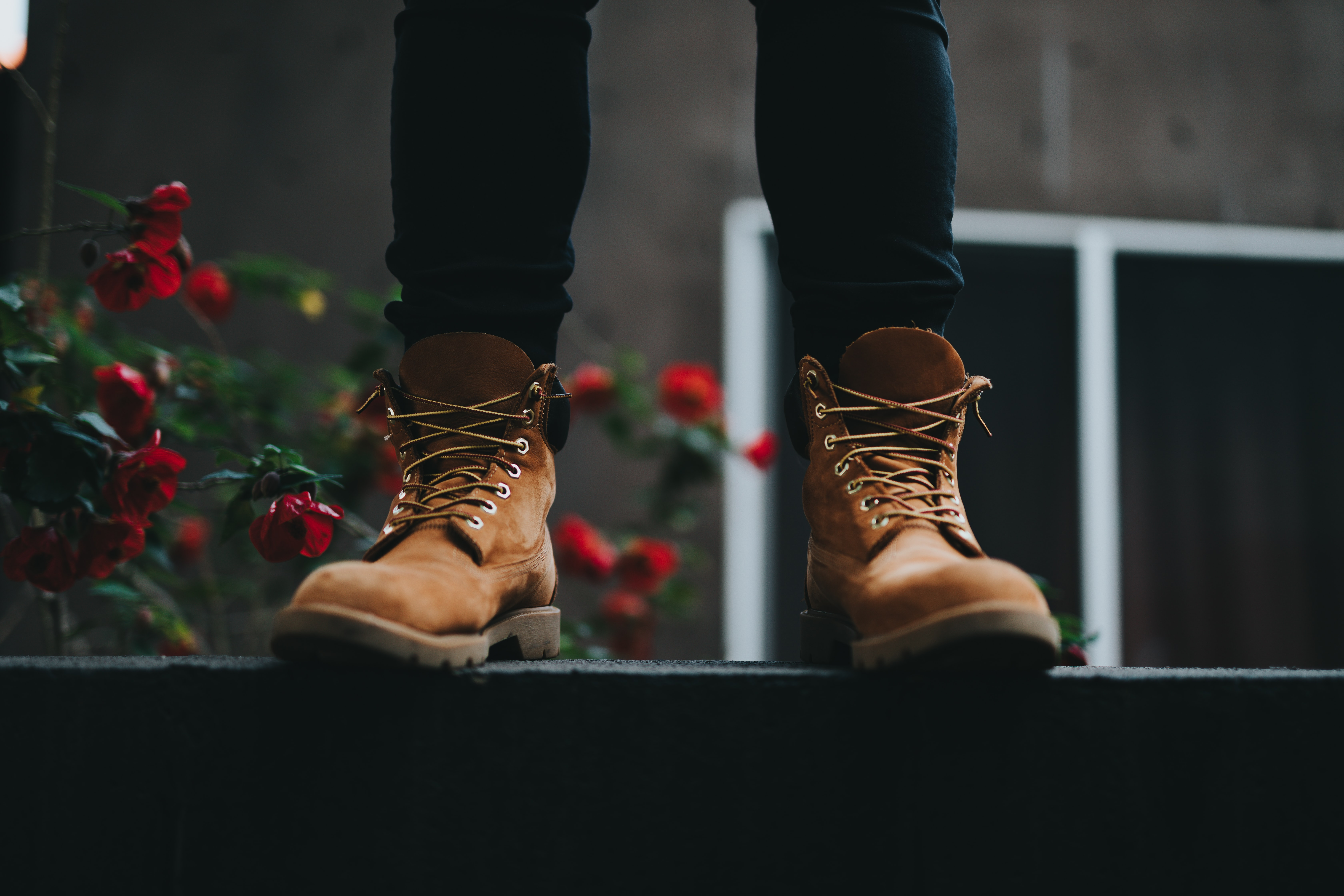 person wearing brown boots standing near red flowers