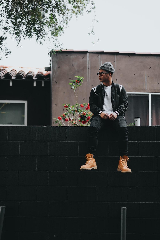 man sitting on black brick fence