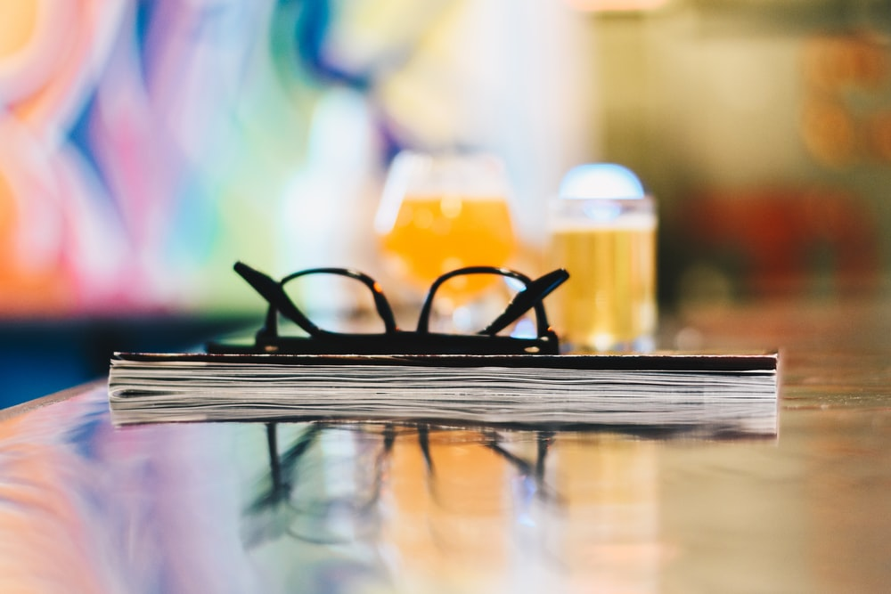 black eyeglasses on closed book on table selective focus photography