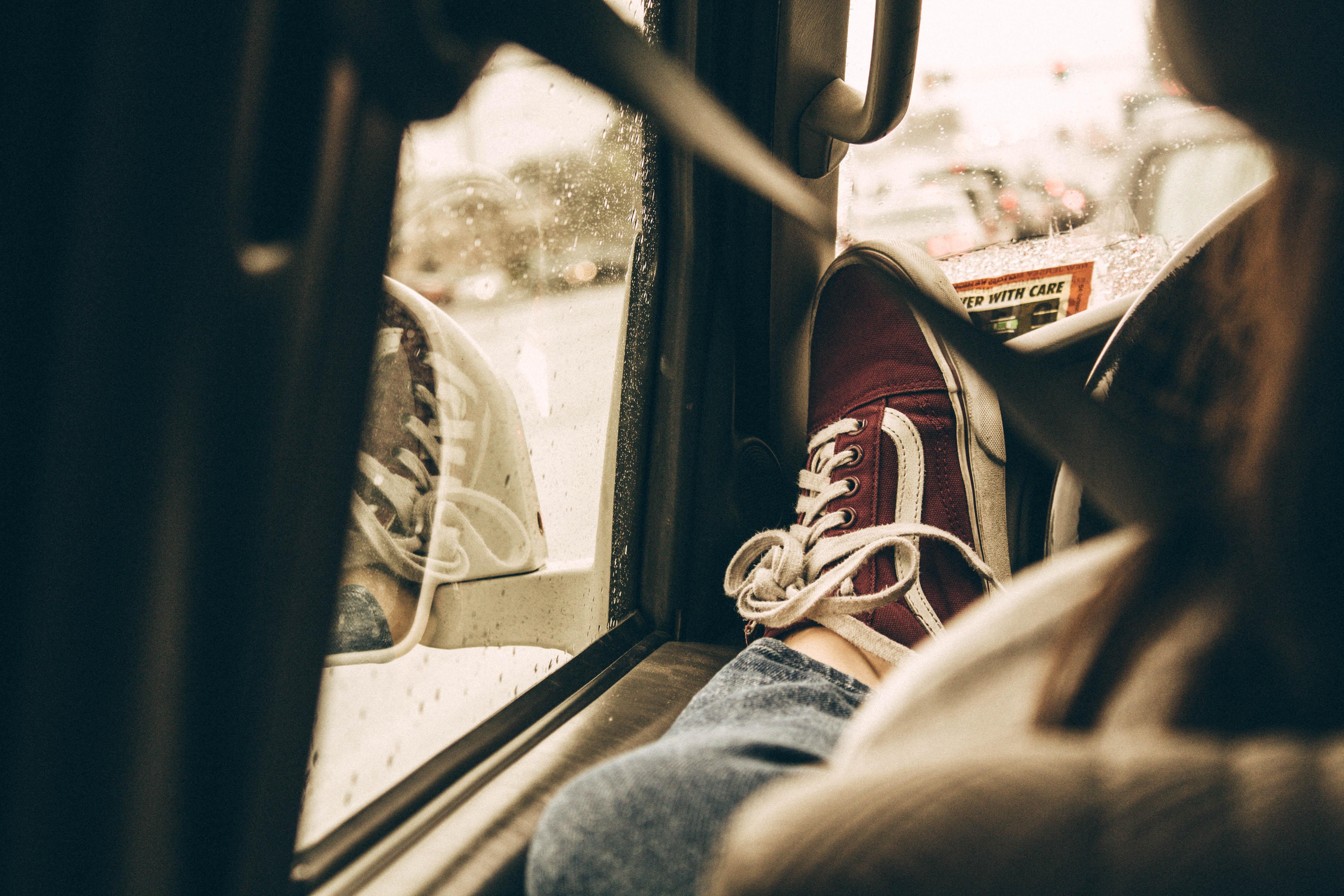 person raising foot beside vehicle steering wheel