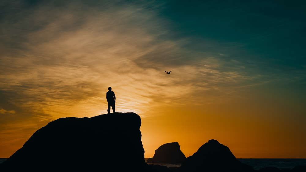 silhouette of man on cliff under blue sky during golden hour