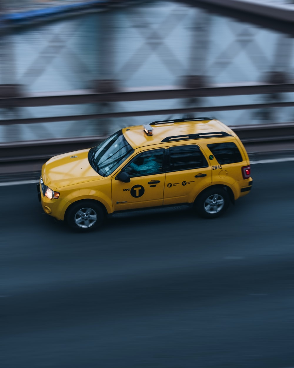 time lapse photo of yellow SUV on road