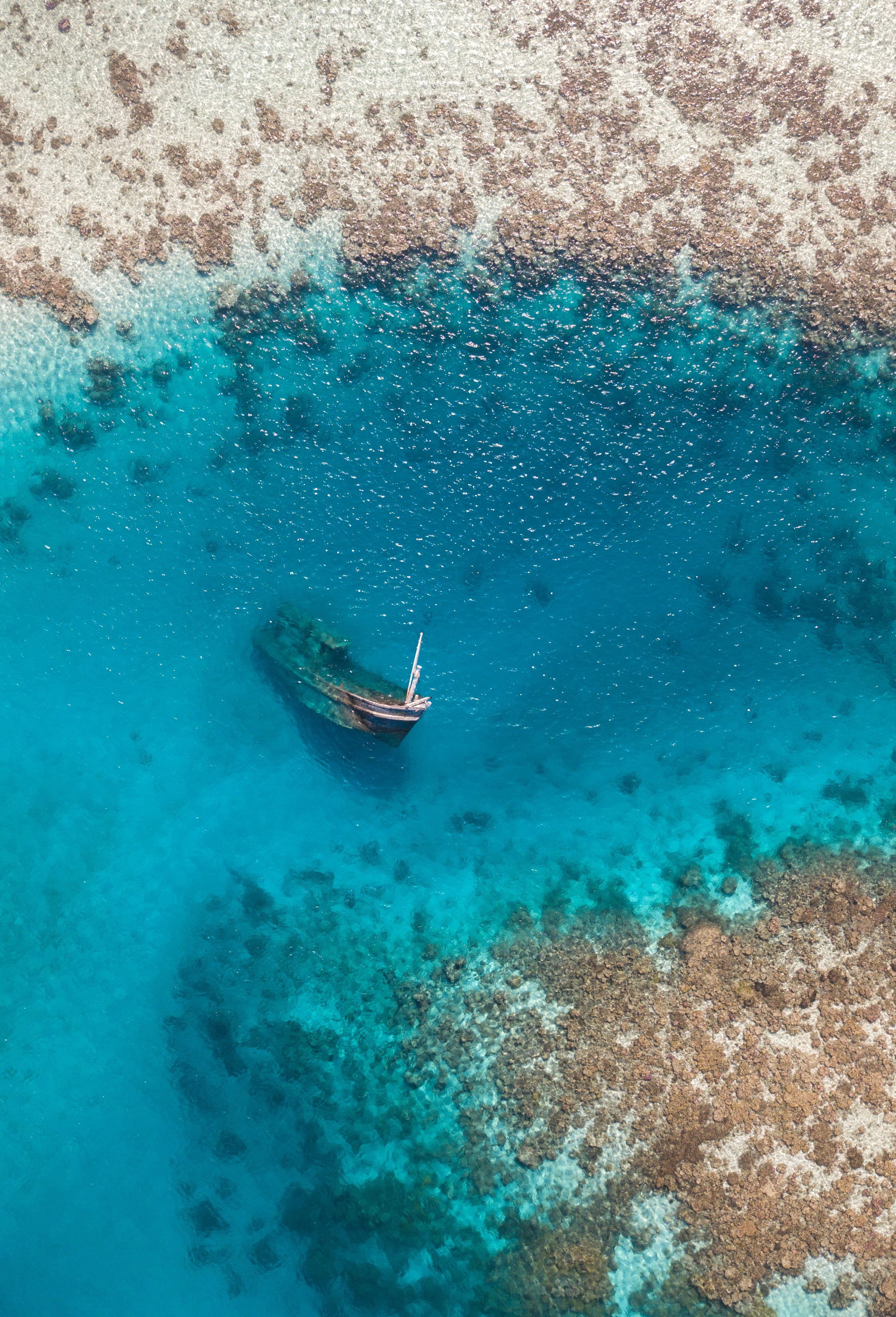 aerial photo of grey boat sink at the blue sea water
