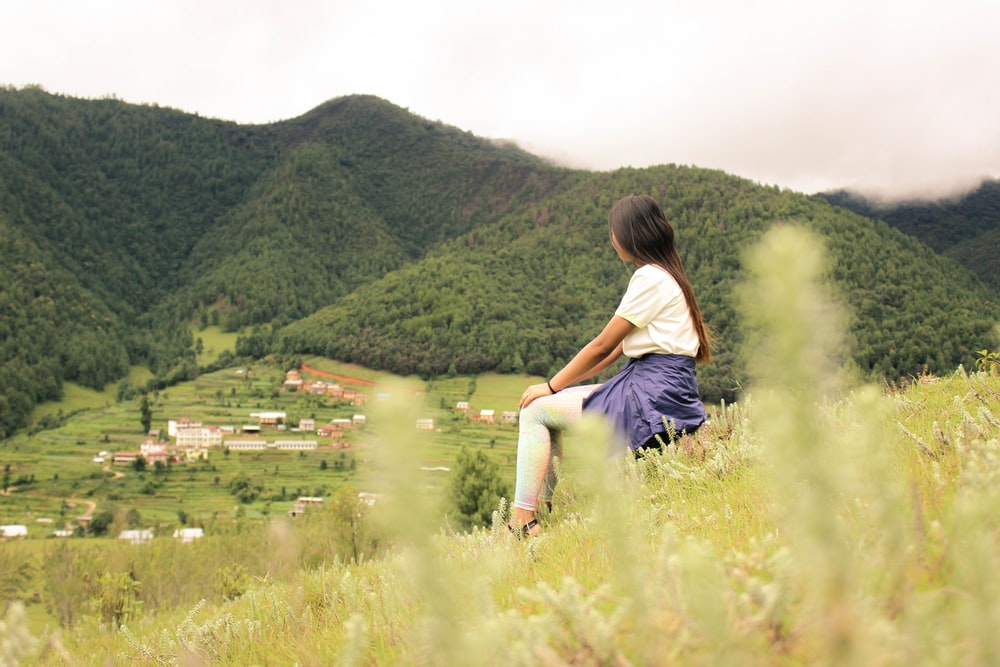 woman sitting on hill covered by green grass during daytime