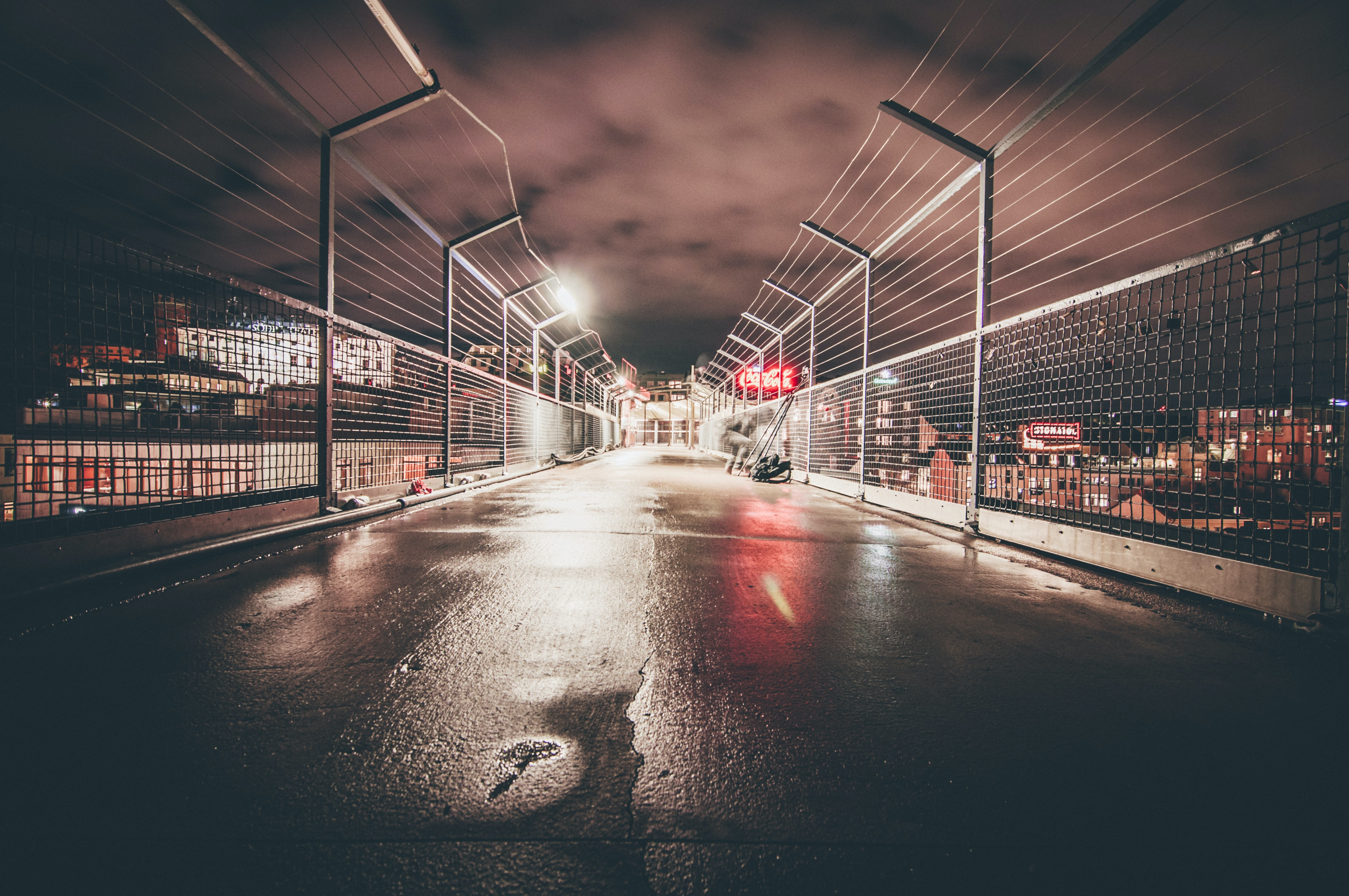 concrete pavement enclosed with chain fences at night time