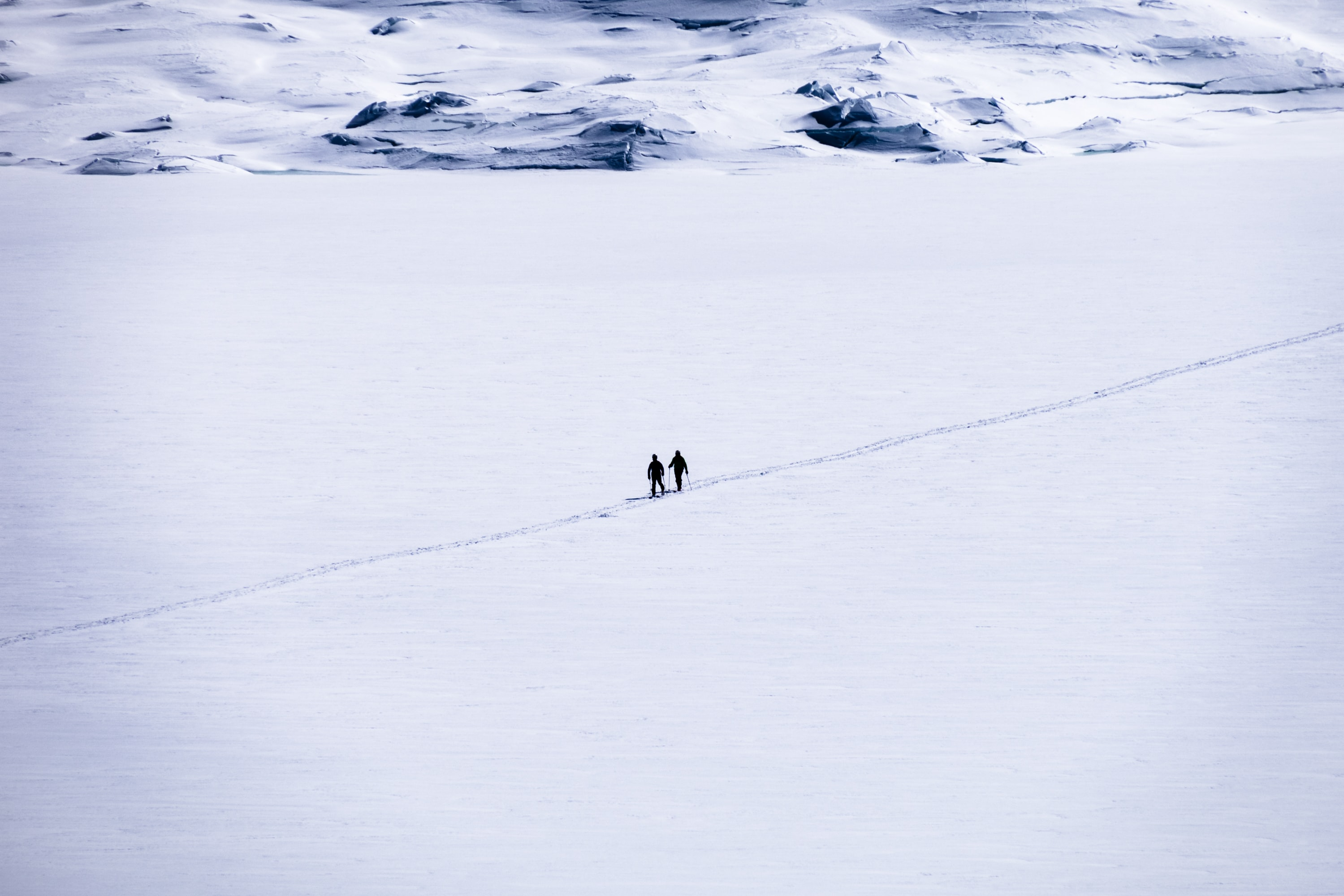 two person walking on snow field
