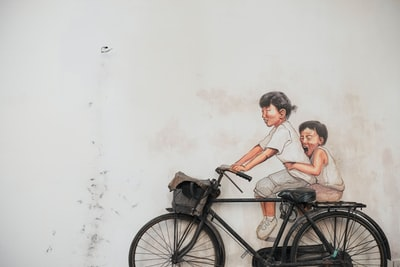 two children riding bicycle painting