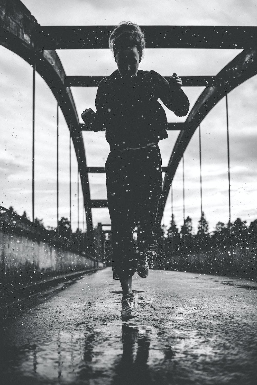 greyscale photography of woman running on bridge