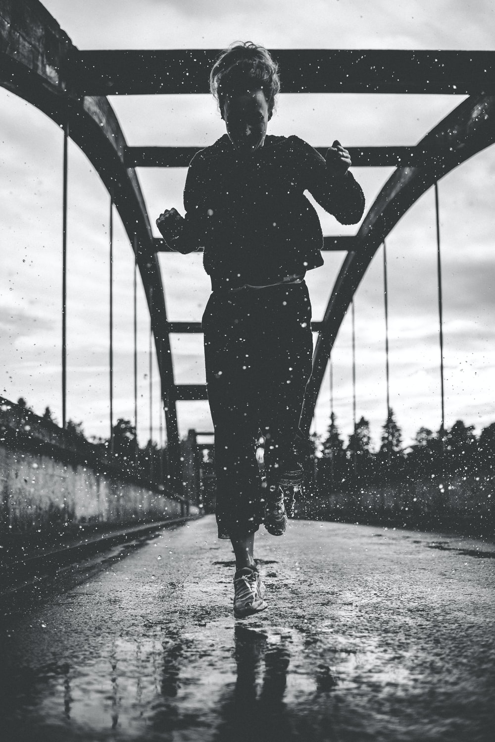 greyscale photography of woman running on bridge