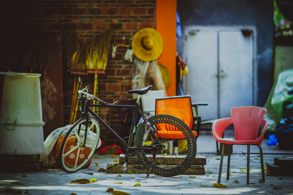 bicycle leaning on wall beside armchair
