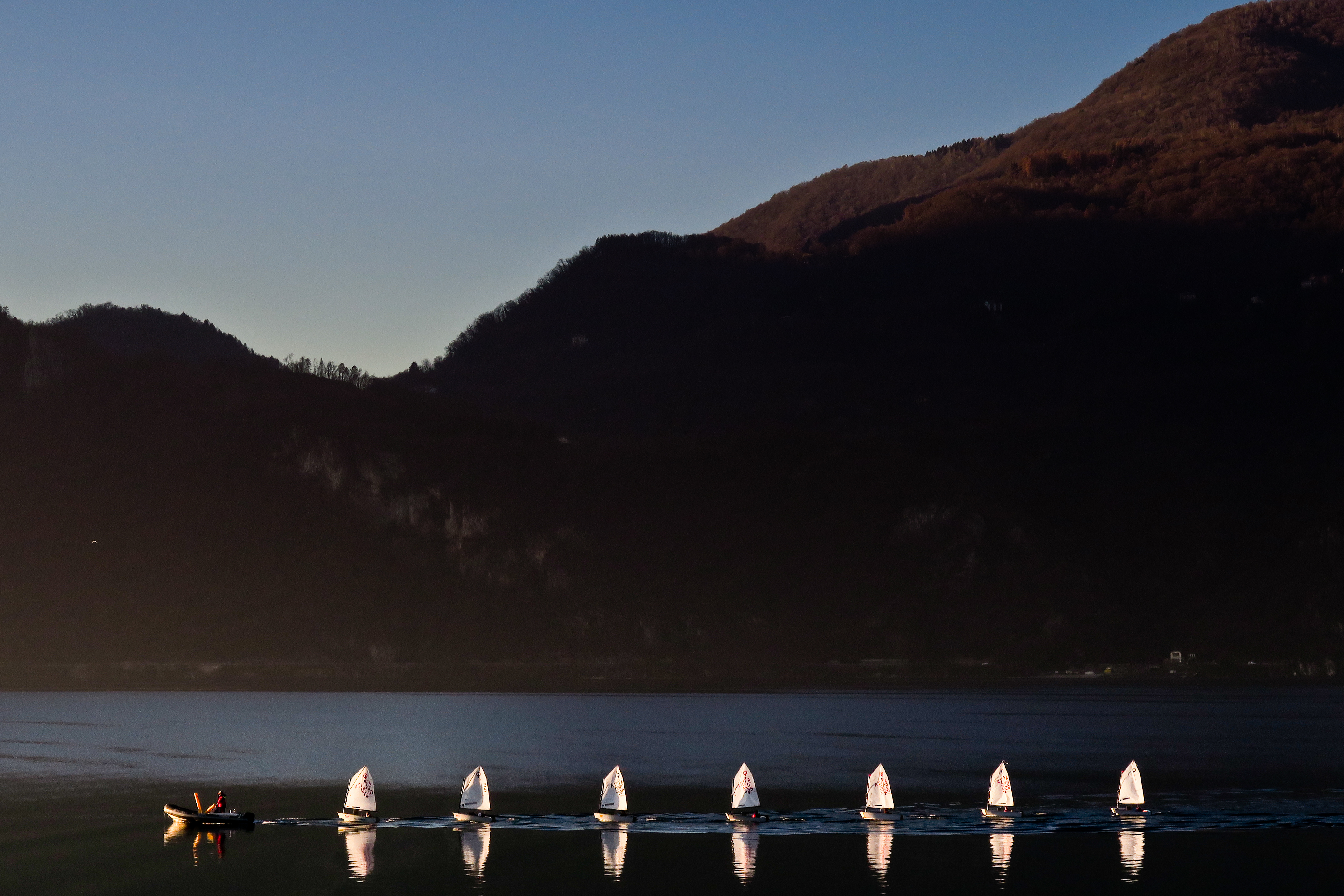 Como lake (Italy). The boats of Optimist Class go back to the harbor after the regatta.